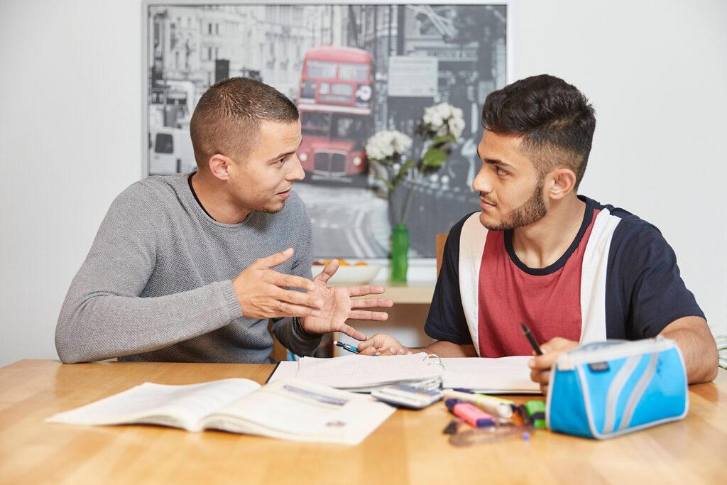 Foto Person rechts: Balazs Petik, Teamkoordinator in der Wohngruppe Gremmendorf erklärt Jugendlichem (Person links)aus Afghanistan Hausaufgaben