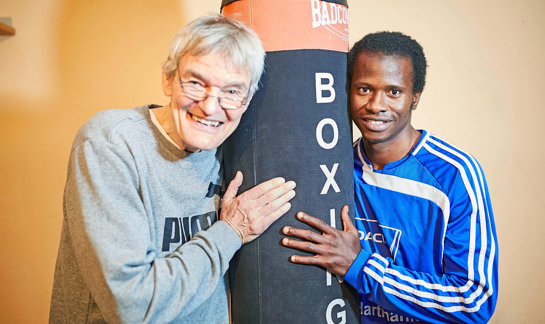 Foto: Älterer Trainer und junger Sportler mit Boxsack inder Mitte, Peter Umlauf betreut die Jugendlichen auch im Fitnessraum
