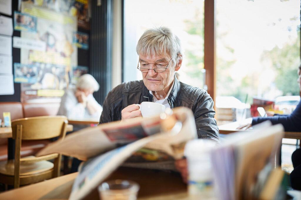 Foto: Älterer Mann sitzend im Café mit Zeitung und einer Tasse Kaffee in der Hand, Peter Umlauf, Ehrenamtler in der Sprachförderung der Kinder-, Jugend- und Familiendienste