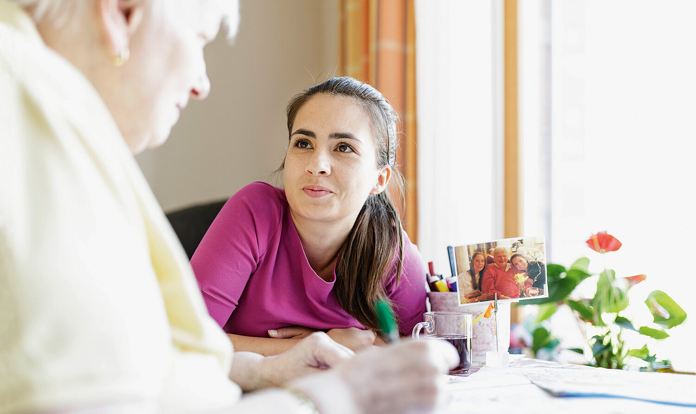 Foto: Sitzende, junge Frau (Monica Elsenback, Pflege-Auszubildende im Handorfer Hof) schaut zu einer älteren Frau