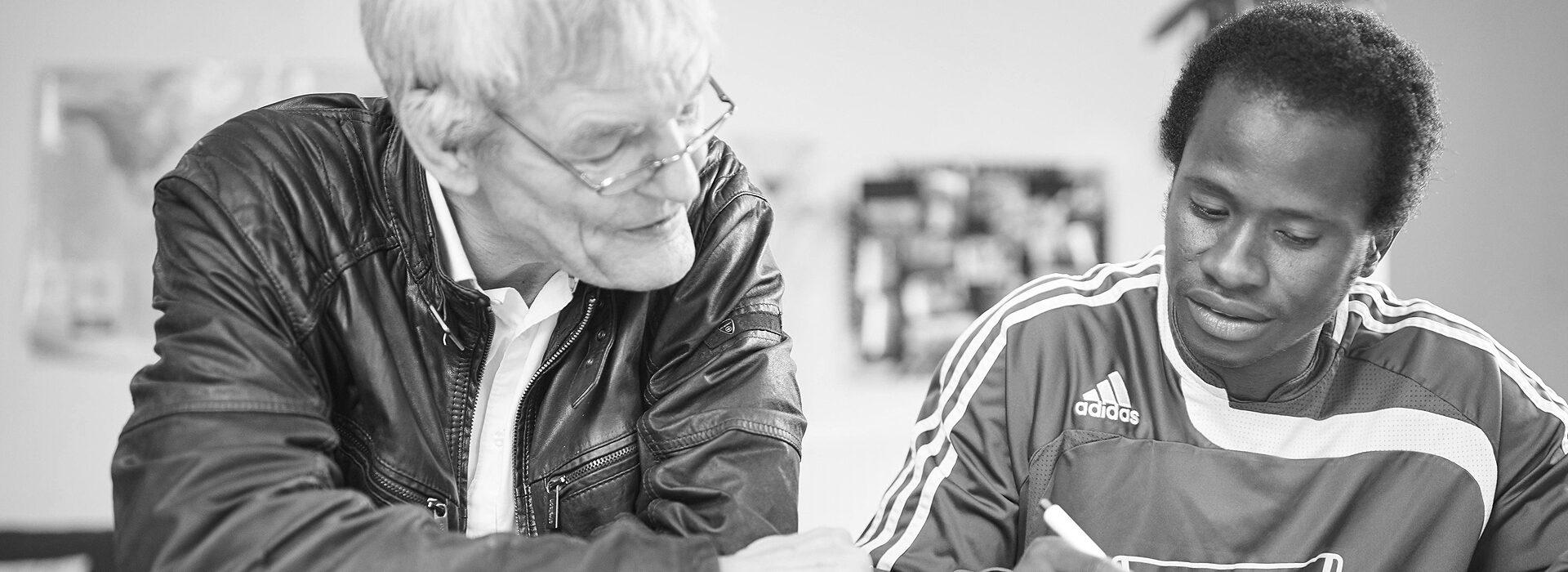 Foto: älterer Mann und Junge beim Lernen